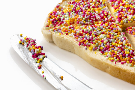 hundreds: Fairy bread with butter knife, side view.  Traditional Australian childrens party food, hundreds and thousands candy sprinkles on white bread.