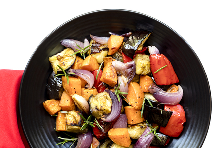 over black: Roasted vegetables on black platter.  Top view over white with red cloth. Stock Photo