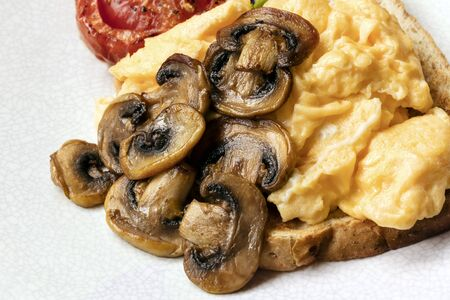 scrambled: Scrambled eggs on toast with mushrooms and roasted tomato.