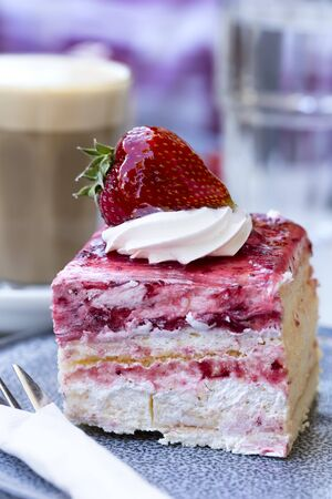 Strawberry sponge cake with cream, with latte coffee behind.  Outdoor setting, focus on strawberry.