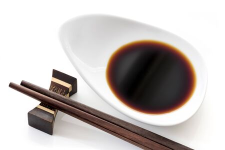 Dish of soy sauce with chopsticks, over white.