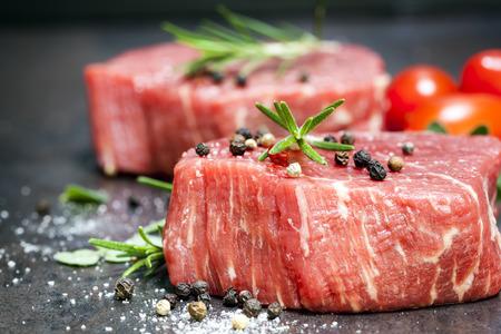 スパイス、ハーブの暗いスレート上のチェリー トマトと牛肉のステーキ。