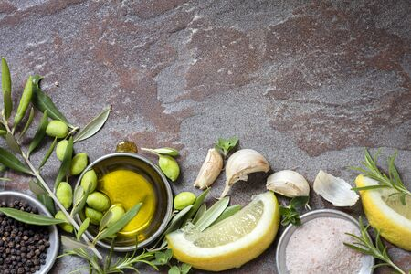 Food background top view over slate. Olives, oil, lemon, garlic, spices and herbs.