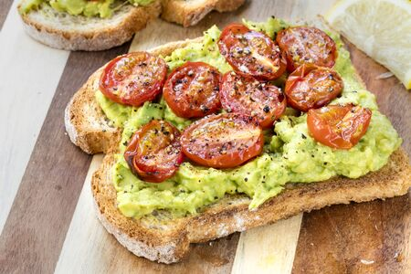 Avocado toast with roasted cherry tomatoes.  Side view, on board. 免版税图像