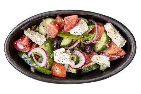 Ensalada griega en el tazón de fuente negro rústico, la vista superior, aislado en blanco.