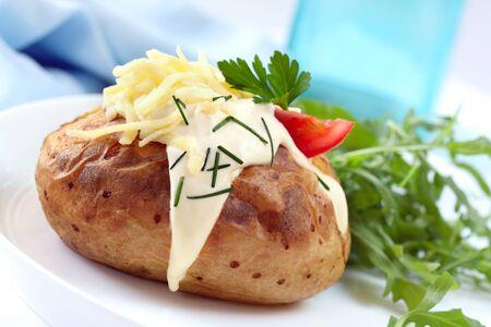 cebollines: Papa al horno con crema agria, queso rallado, cebollín y ensalada. Foto de archivo