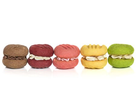 Row of colorful cream cookies or maracoons, isolated on white. Stock Photo