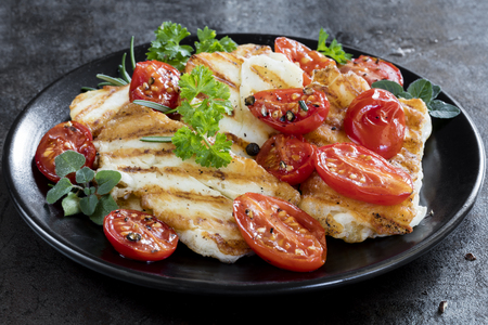 Halloumi cheese, grilled, with roasted cherry tomates and herbs. Banco de Imagens