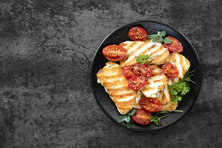 Halloumi cheese, grilled, with roasted cherry tomates and herbs. Top view over dark slate.