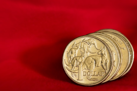 Australian one dollar coins over vibrant red background, with copyspace.