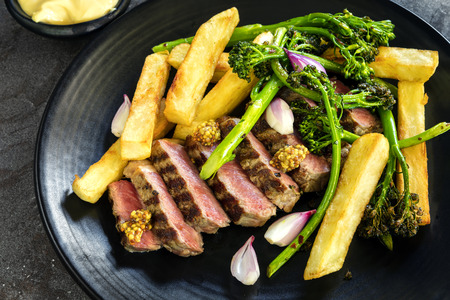 Steak and chips with broccolini, wholegrain mustard, pickled shallots and bearnaise sauce.  Sliced porterhouse. Stockfoto