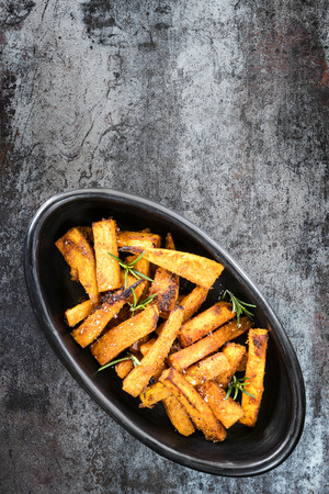 Sweet potato fries in black bowl, top view over slate.