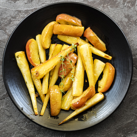 Roasted parsnips with apple and thyme, on black serving platter, top view.