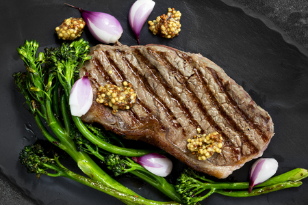 Porterhouse steak, grilled with broccolini, pickled shallots and mustard.  Top view on slate.