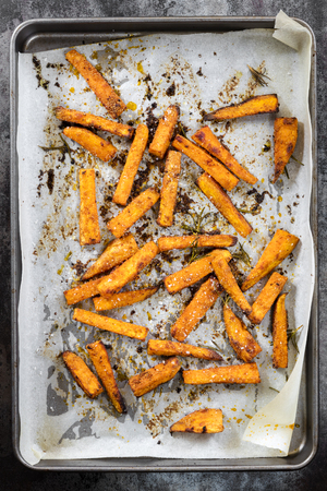 Sweet potato fries on oven tray, top view.  Baked with paprika, rosemary and salt.