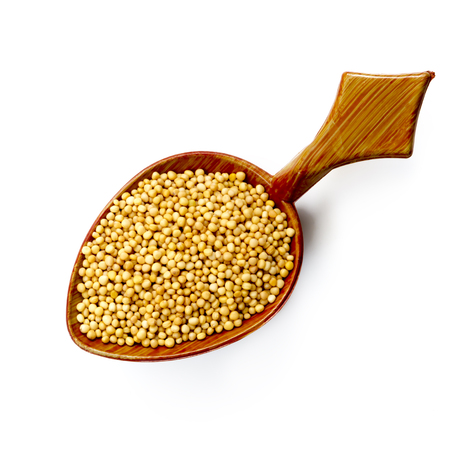 Yellow mustard seeds on wooden spoon, isolated on white, top view.