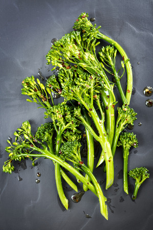 Broccolini with chili flakes and olive oil.  Top view on slate.