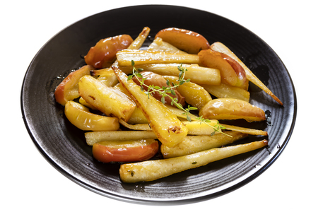 Roasted parsnips with apple and thyme, on black serving platter.