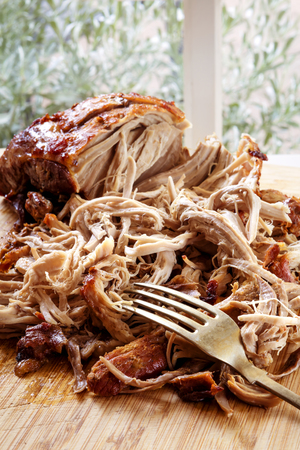 Pulled pork roast on board with fork.  Delicious shredded meat. Stock Photo