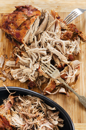 Pulled pork roast on board with forks.  Delicious shredded meat.