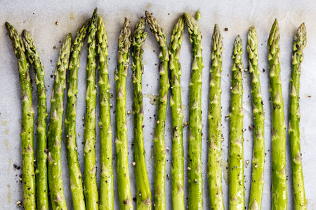 Asparagus spears on parchment paper over oven tray, ready for roasting.  With olive oil and pepper. Stockfoto