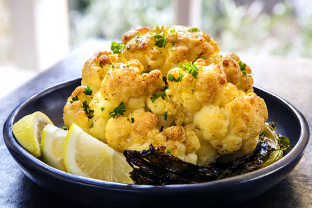 Roasted whole cauliflower with lemon in black serving dish on slate table.