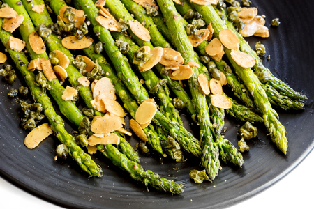 Roasted asparagus with toasted almond flakes and capers.  Black plate over white.