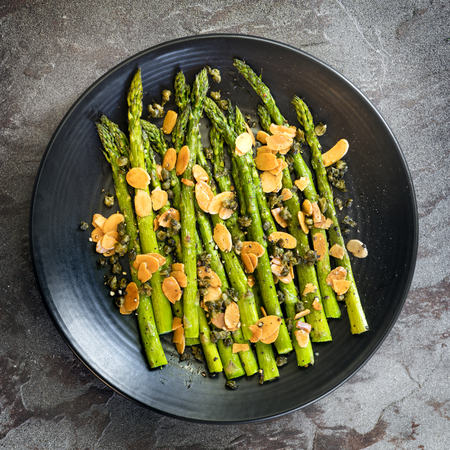 Roasted asparagus with toasted almond flakes and capers.  Black plate over slate, top view. Stockfoto