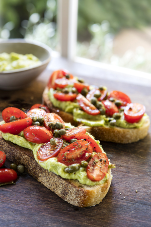 Avocado toast with cherry tomato and caper salsa.  Sourdough bread.  On old board, with garden view behind. Stockfoto