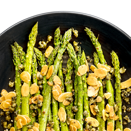 Roasted asparagus with toasted almond flakes and capers.  Black plate, top view over white.