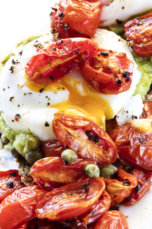 Poached egg on toast with avocado, roasted cherry tomatoes, and capers.