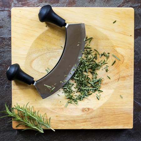 Chopping fresh rosemary with mezzaluna curved knife on board, top view on slate.