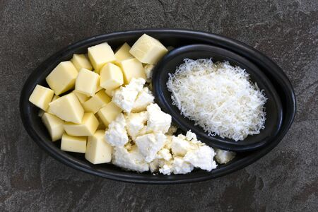 Mozzarella, ricotta and parmesan Italian cheeses, top view in rustic black dish over slate.
