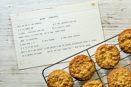 Anzac biscuits on rack with vintage typewritten recipe.  Top view on rustic timber.