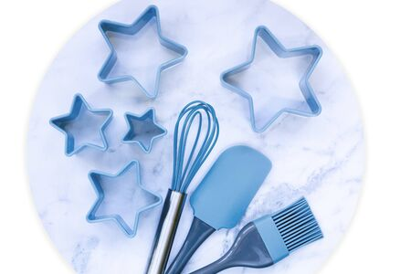Blue baking utensils top view on marble  isolated.