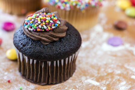 Chocolate cupcake with frosting and sprinkles, on floured board.