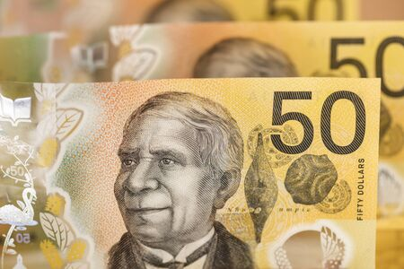 Australian money background.  Fifty dollar notes in soft focus over white. New plastic notes issue.