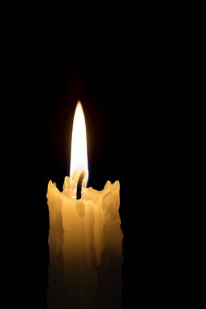 Candle flame with black background.  Single candle burning, with melted beeswax. Stockfoto
