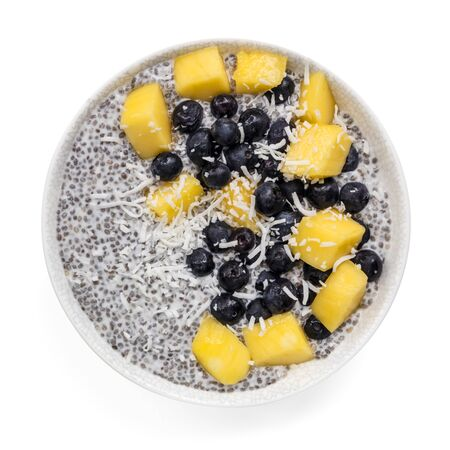 Chia seed pudding with mango, blueberries and coconut.  Top view, isolated on white.