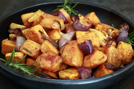 Roasted sweet potato with red onion and rosemary, in black dish, side view.