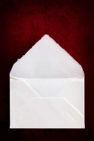 Vintage white envelope, top view, over rich red brocade background.