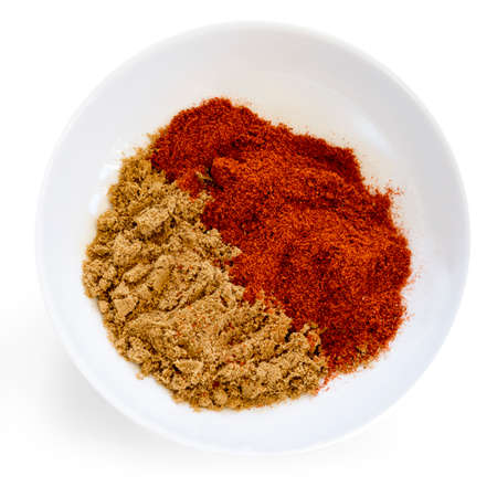 Cumin and paprika in small white bowl.  Top view, isolated.