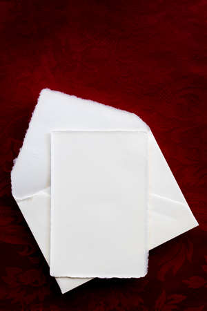 Vintage blank writing paper and envelope, top view over rich rerd background