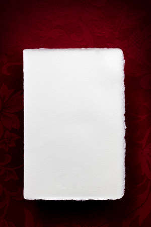 Blank vintage white writing paper over rich red background.