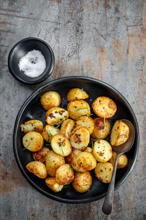 Roasted baby potatoes with wholegrain mustard and rosemary.  Rustic black dish over timber background.