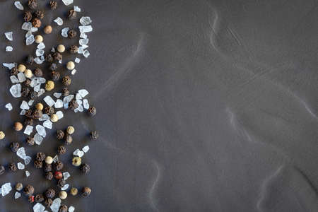 Black peppercorns and rock salt on slate, top view, flat lay. Stockfoto