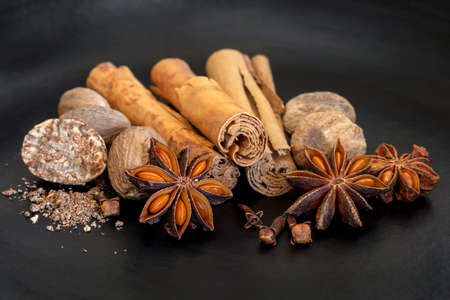 Christmas spices background.  Cinnamon, nutmeg, star anise and cloves on rustic black plate