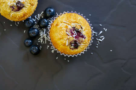 Blueberry and coconut muffins with ingredients, top view on dark slate.  Homemade baking. Stockfoto