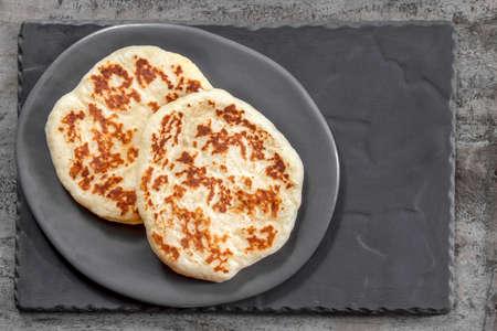 Homemade flat bread on rustic gray plate. Top view.  Delicious yogurt pita. Stockfoto