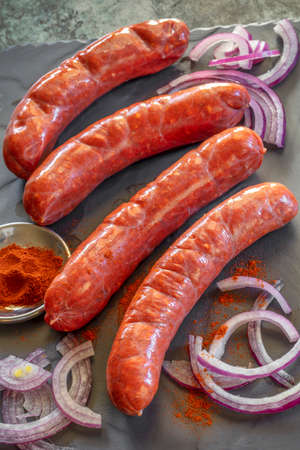 Fresh uncooked chorizo sausages with paprika and red onion.  Side view on dark slate. Stockfoto